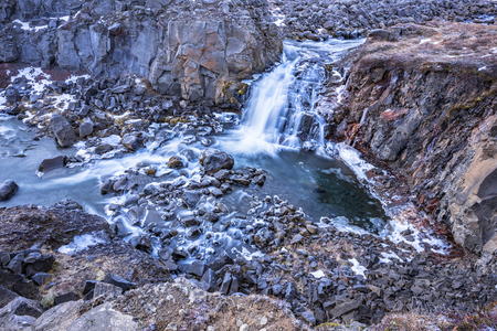 rugged terrain:  A waterfall in Iceland cascades down the side of a rugged mountain into a natural pool