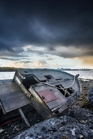 An old abandoned fishing vessel from the early 1900s rests on a remote beach as it rots, exposing the ships wooden ribs and hull infrastructure.    Stock Photo