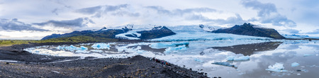 fjallsarlon:   Panorama image of Icelands Secret Lagoon.  The site is full of glaciers and icebergs surrounded by mountains and a rocky, rugged shoreline. Shot with seven images.   Stock Photo