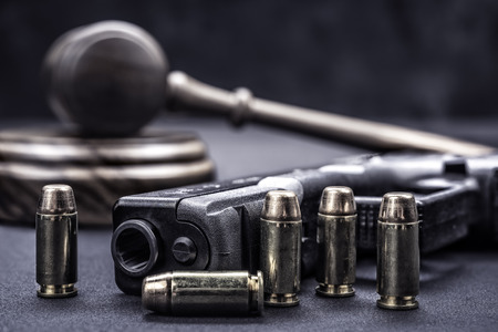 A handgun with bullets symbolizing gun rights while framed with a judge's gavel and block.