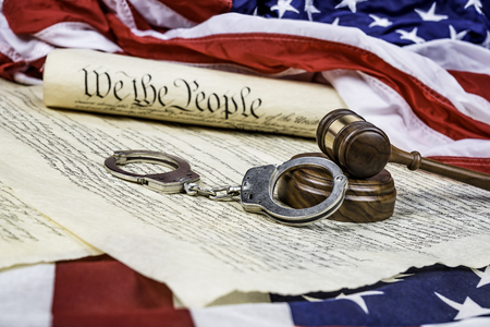 restraints: The United States Constitution rolled up on an American flag with a gavel and handcuffs in the foreground.  Stock Photo