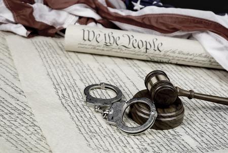 アメリカ合衆国憲法は、小槌とフォア グラウンドで手錠アメリカ国旗にロール アップされます。