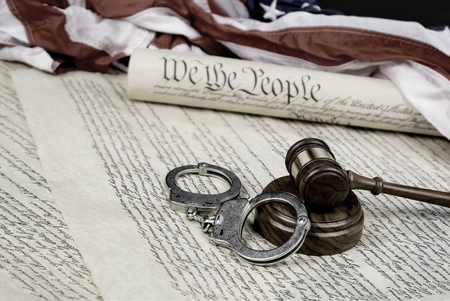 restraints: The United States Constitution rolled up on an American flag with a gavel and handcuffs in the foreground.