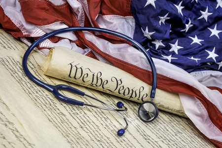 The United States Constitution rolled up on an American flag with a medical stethoscope symbolizing the need for good healthcare Stock fotó