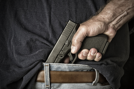 A man with a pistol in his waistband grasps the handle in preparation for pulling the weapon photo