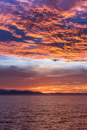 A beautiful sunrise in the remote Channel Islands in California shows the vibrant and moody brilliantly red and orange sunlit clouds.