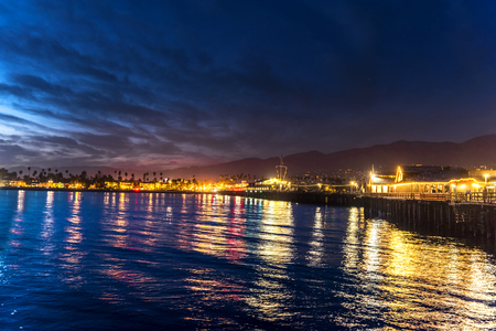 Image of Stearns Wharf at night in Santa Barbara California shows the brilliant lights of a lively city destination. Stock Photo