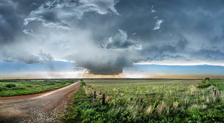 Panoramic image of a large, powerful tornadic supercell storm moving over the Great Plains during sunset, setting the stage for the formation of tornados across Tornado Alley. Banque d'images
