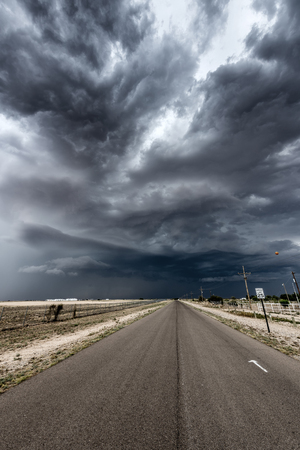 A massive, dark thunderstorm forming over a long, narrow road in Tornado Alley, Oklahoma. 版權商用圖片