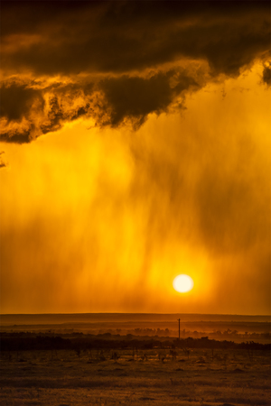 Pouring rain during a lightning storm framed by a low, orange sunset shot in the Great Plains Tornado Alley, Roswell, New Mexico.