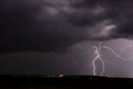 A mezocyclone lightning storm with dark clouds forming over a small town in Tornado Alley, Oklahoma at night Stock Photo
