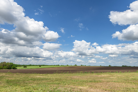 White, puffy clouds moving over remote dirt road and flat lands in the Great Plains, Oklahoma. 스톡 콘텐츠
