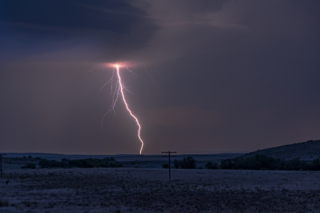 A large lightning strike at dusk in an open plain framed against a deep, dark orange sunset and stormy skies. Stock Photo