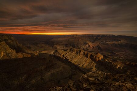 A view of the rugged yet beautiful Grand Canyon national park during a dramatic sunset with the moon rising to light the canyon at Lipan Point.