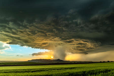 Panorama of a massive mesocyclone weather supercell, which is a pre-tornado stage, passes over a grassy part of the Great Plains while fiercely trying to form a tornado.