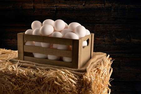A small wooden crate of freshly collected eggs sitting on burlap and a hay bale in a barn. Image shows the freshness associated with country living.