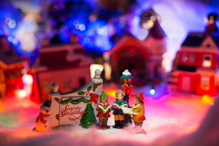 kids reading bible next to holiday greeting sign with snowy christmas village in the background. Holiday greeting miniature scenery concept Reklamní fotografie