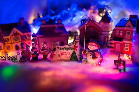 holiday greeting sign with snowman holding star stands kid choir in front of a christmas village