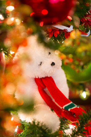 Christmas backgroud.  A white teddy bear with red Christmast scarf hanging on Christmast tree in focus and the foreground is the bokeh made of glittery shinning ornaments and tree leaves