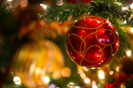 Red glittery Christmas ornament ball hang on tree leaves in focus against the bokeh background of gold green shinning with lights