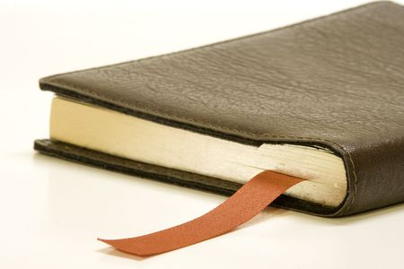 Old book with ribbon bookmark against white background. Stock fotó