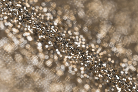 shinning light: Gold glitter abstract background with a selective focus strip through the middle