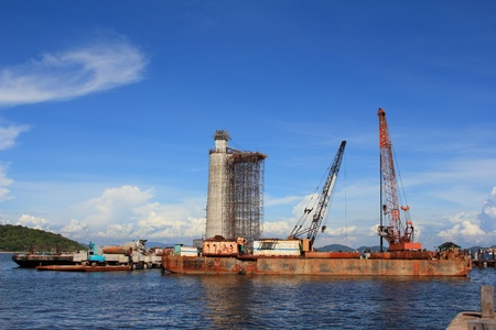 marine industry: the lighthouse under construction and cranes under a blue sky  Stock Photo