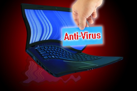 The laptop computer and  hand pick a label with word Anti-Virus photo