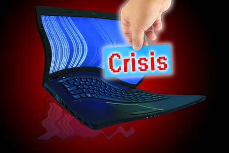 The laptop computer and  hand pick a label with word Crisis photo