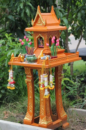 Thai outdoor spirit house shrine.In modern Thailand all spirit houses are kept outdoor. This one is made in the Thai Buddhist temple (wat) style. photo
