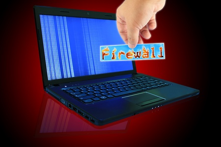 programmed: The laptop computer and  hand pick a label with word Firewall Stock Photo