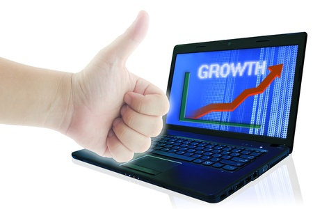 Hand showing thumb up and growth trend of the arrow graph on computer screen. Growth Business Concept. photo
