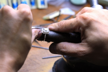 jeweller: Close up of repairing ring on wood stick tool