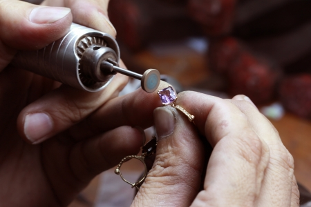 gold jewelry: Close up of repairing ring by polishing motors tool