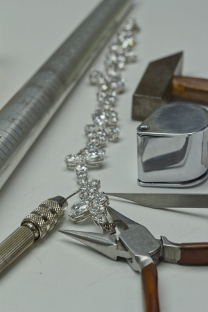 Repairing jewelry tools  loupe,wrench,pliers,hammer  and bracelet with diamond