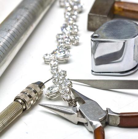 Armband met diamanten en repareren van sieraden gereedschappen loupe, moersleutel, tangen, hamer Stockfoto