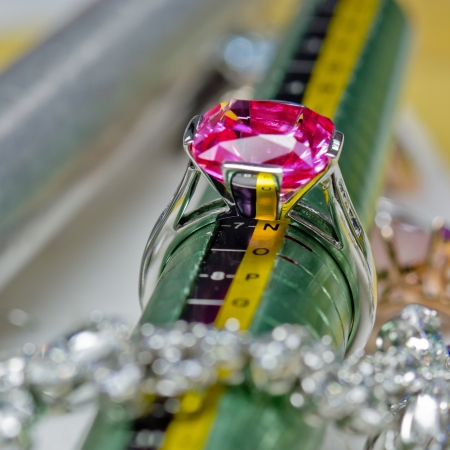 White gold ring with ruby and a green ring size stick