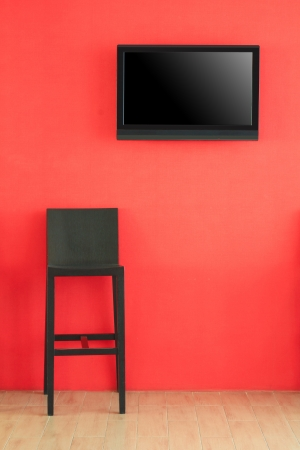 Modern LCD screen on red wall and black chair in front of presentation stage photo