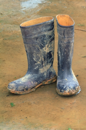 specific clothing: Muddy rubber boots on wet ground Stock Photo