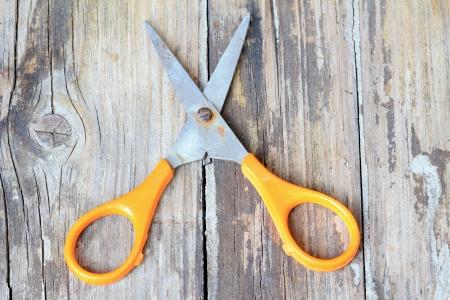 Yellow scissors on old wood