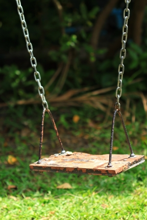 Old wood swing hanging in garden, green background.