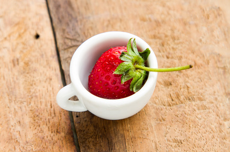 Strawberry in a glass placed on a wooden table. Stock Photo