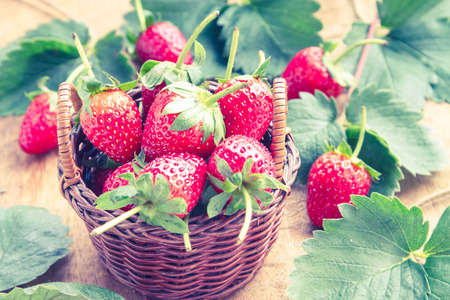 Strawberry fresh and tasty ingredients in a cup on a wooden table made of old and vintage.