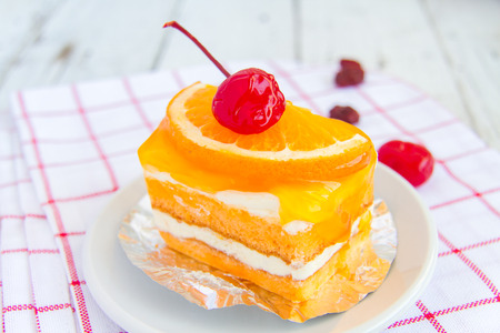palatable: Orange cake with a cherry red delicious and palatable. Stock Photo