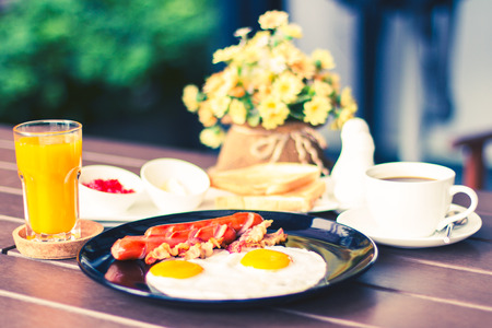 beneficial: Breakfast with bacon, fried egg and orange juice are beneficial to health with a vintage image. Stock Photo