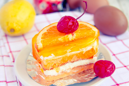 palatable: Orange cake with a cherry red delicious and palatable and color reproduction vintage. Stock Photo