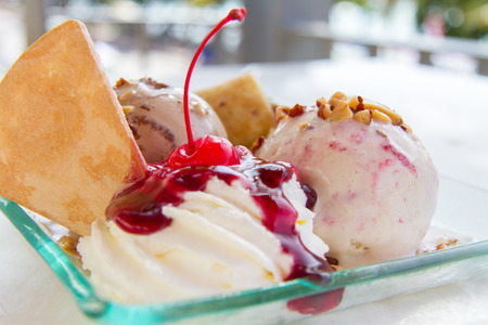 ice cream sundae: Ice cream topped with a sweet blue berries wrapped in a soft dough and cherry red. Stock Photo