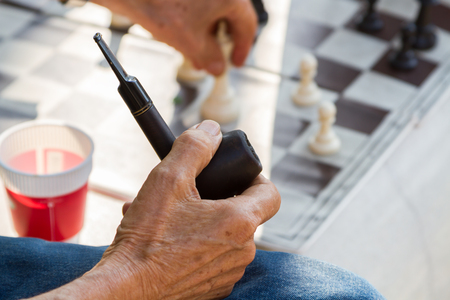 unhealthy thoughts: The old man sat smoking a pipe that is harmful to health and the people around you are playing a game of chess at the idea.