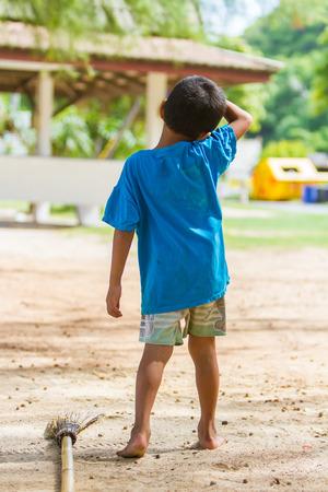 niños pobres: Barrer las hojas en los niños pobres y ayudar a las familias. Foto de archivo