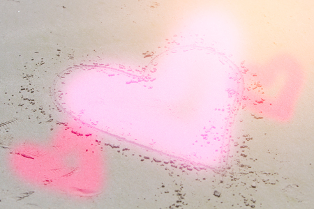 Draw a heart on the beach to show the love for color and dye making a heart shape.